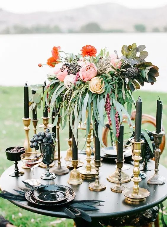 black candles, feathers and dishes add an ambience to this tablescape