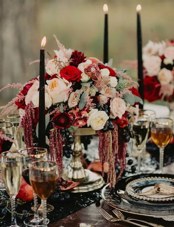 very lush flower and grapes centerpiece with black candles and a black table runner