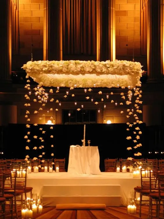 gorgeous wedding chuppah decorated with white blooms and candles