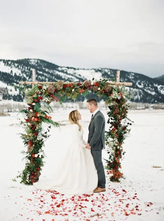 gorgeous outdoor wedding arch with leaves, fir, bold blooms and fruit