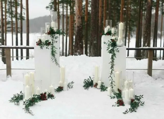 outdoor winter altar with candles and greenery that shows up the scenery
