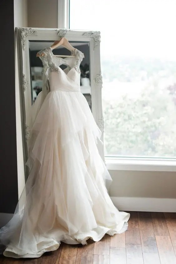 gorgeous bridal dress hung on a vintage mirror