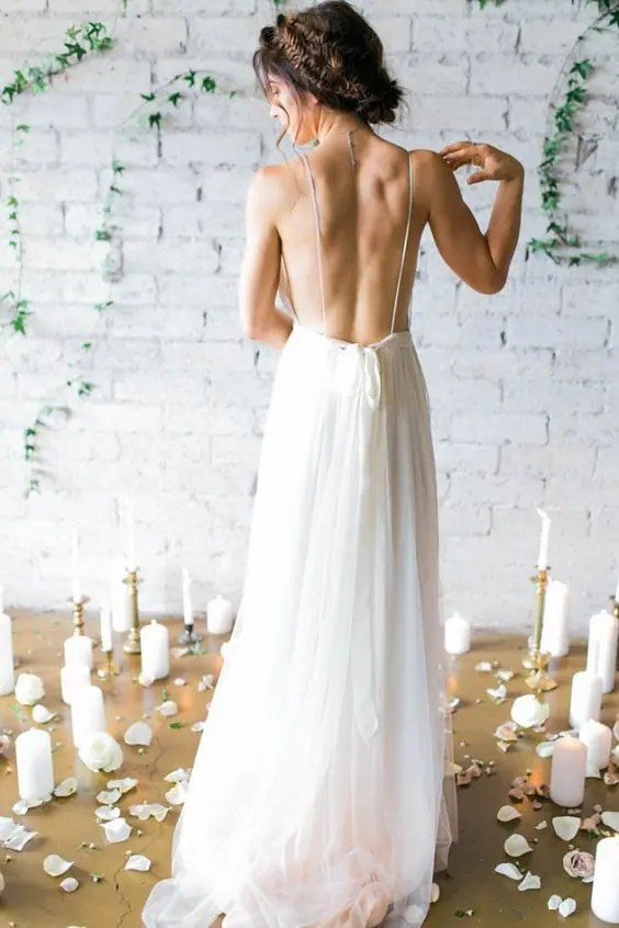 bride showing off her backless dress with thin straps