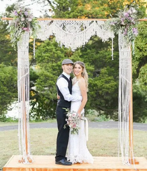 a wedding arch covered with macrame and pastel flowers