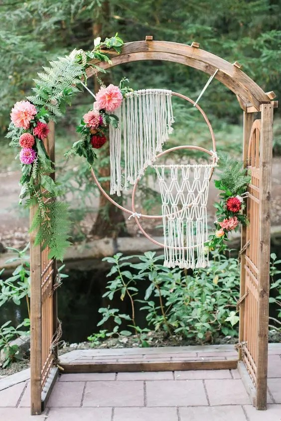 a wooden arch with leaves, flowers and macrame hangings