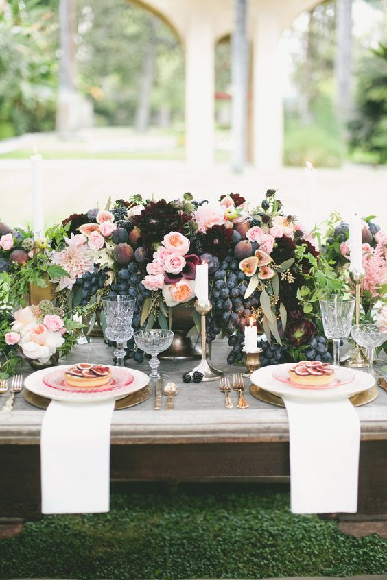 a lush summer centerpiece with blush, plum and burgundy flowers, blackberries, figs and grapes for a summer or fall wedding
