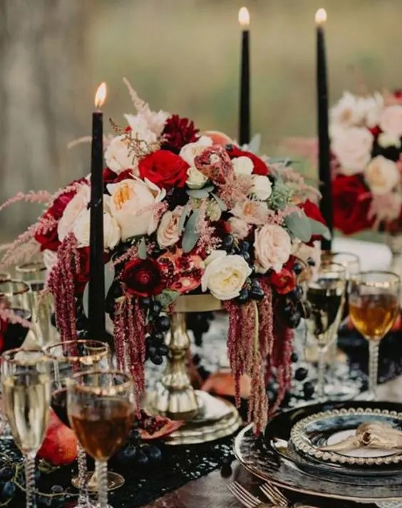 a lush decadent centerpiece with neutral, blush, red blooms and black grapes looks boho lux and jaw-dropping