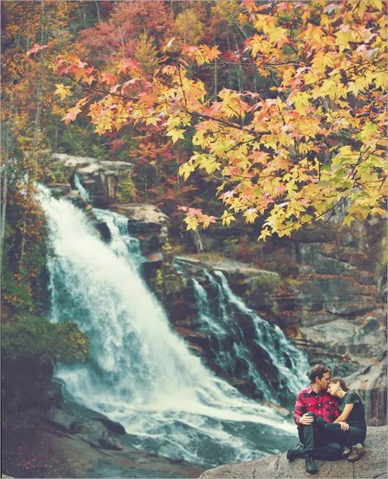 fall forest with a waterfall and a beautiful couple next to it