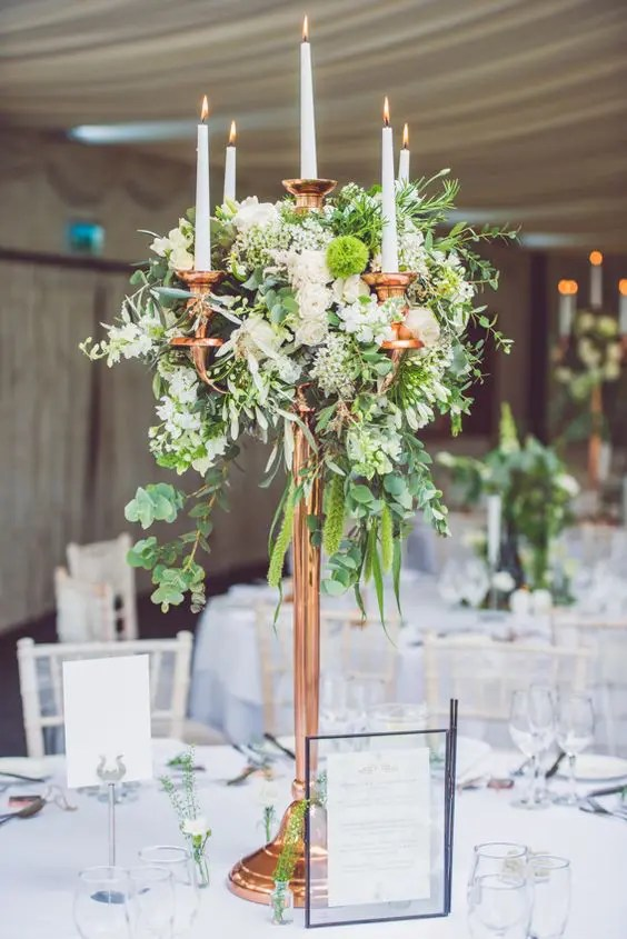 Picture Of A Tall Copper Candle Stand With Lush Greenery