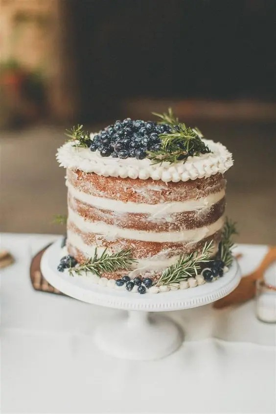 a yummy spiced naked wedding cake with frosting and berries