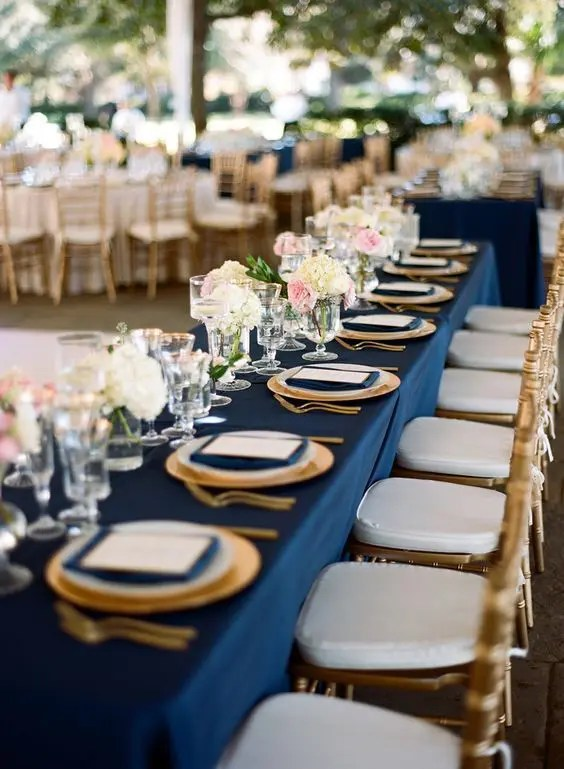 a chic table setting with navy napkins and a tablecloth, gold cutlery and chargers for a chic look