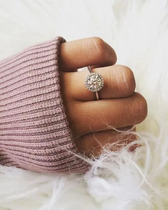 a round diamond engagement ring with a halo around looks girlish and chic