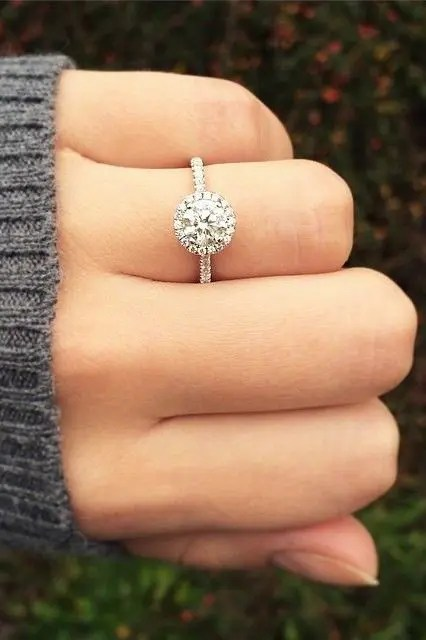 a white gold round diamond engagement ring with a halo is a cute idea