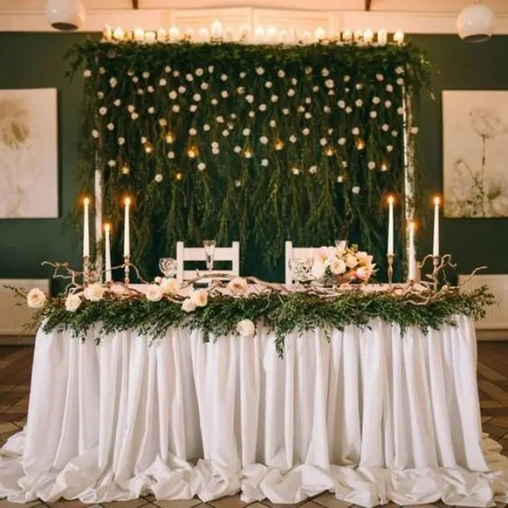 lush greenery with white blooms and candles on top for a woodland-inspired wedding