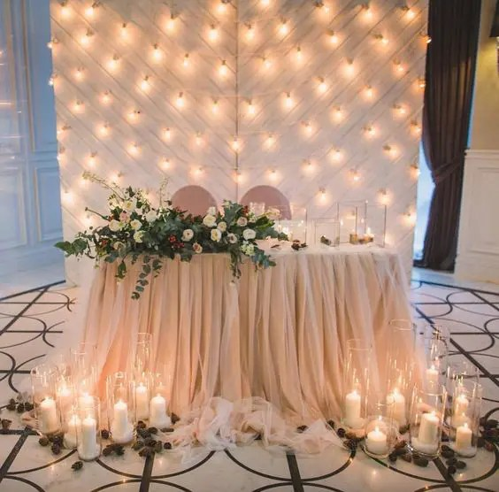 a draped blush fabric backdrop with lots of lights perfectly matches the table decor and looks cute