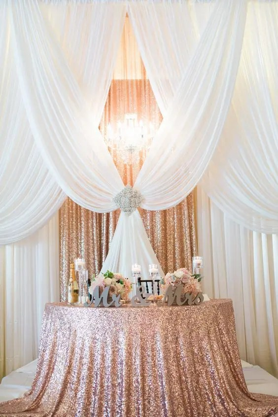 a rose gold sequin fabric backdrop plus white draperies, a large rhinestone brooch and a glam chandelier