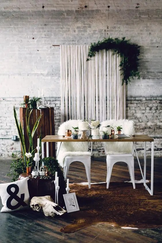 a white fringe backdrop with lush foliage for a boho-inspired wedding