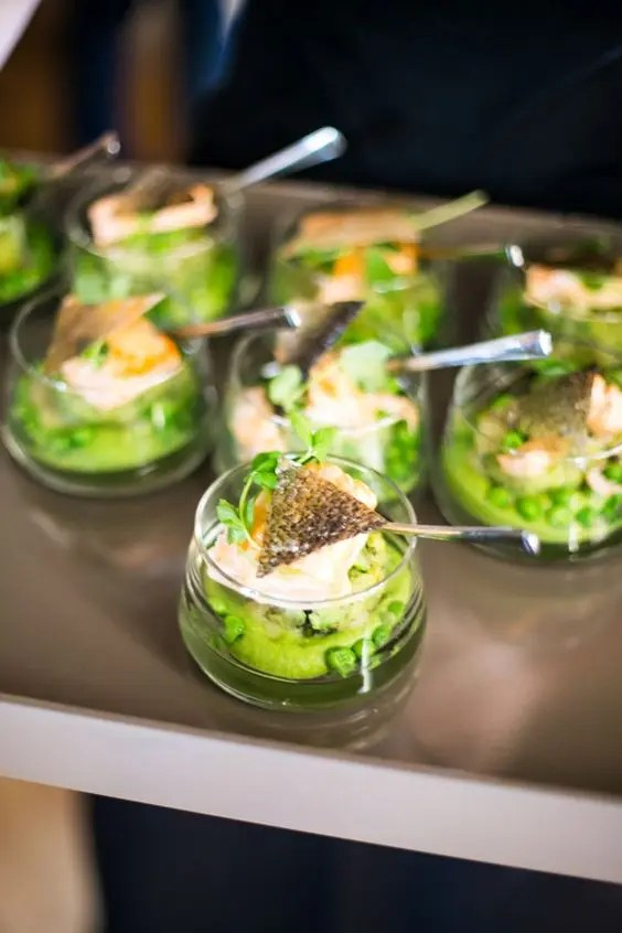 green salad with fresh peas and a piece of steamed fish on top