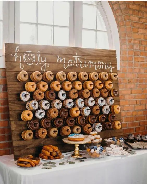 a wooden plaque donut wall is ideal for a rustic wedding and as a backdrop for the dessert table