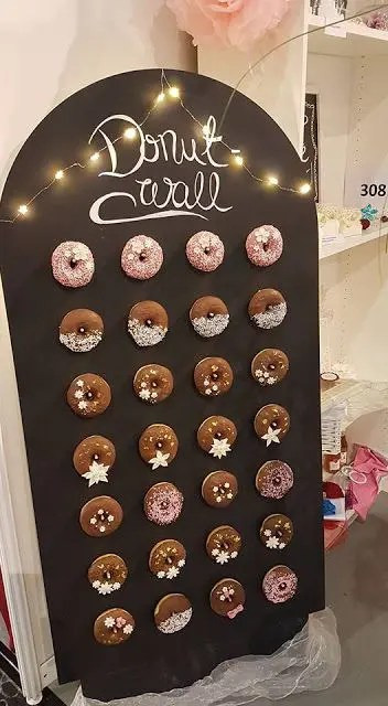 a chalkboard donut wall topped with LED lights is a cute idea