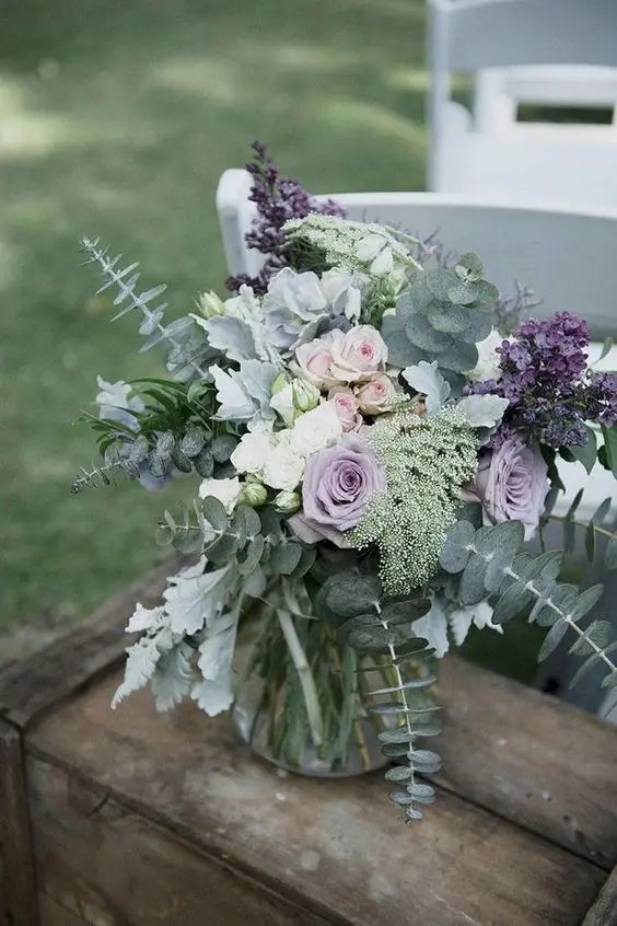 a pale wedding centerpiece with lilac and blush roses, eucalyptus, pale miller and lilac
