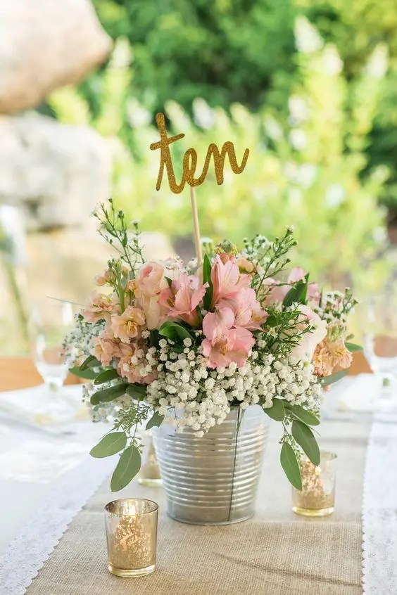 a rustic bucket with pink blooms, baby's breath and a calligraphy table number