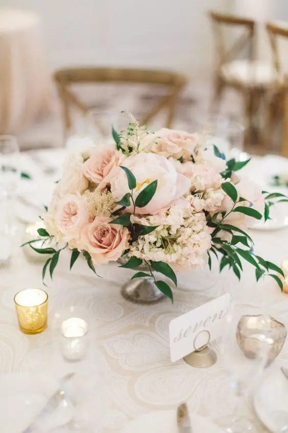a vintage bowl with blush and dusty pink blooms and lush greenery
