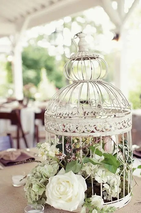 a vintage birdcage with greenery and neutral blooms for a chic centerpiece