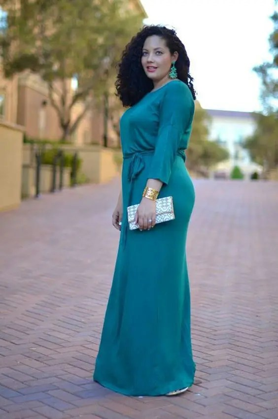 an emerald high neckline long sleeve bridesmaid's dress with matching earrings and a metallic clutch