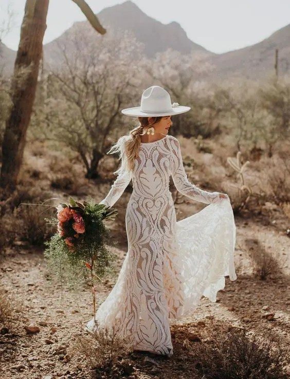 a bride wearing a boho lace sheath wedding dress and a creamy hat with a flower for a boho hipster look