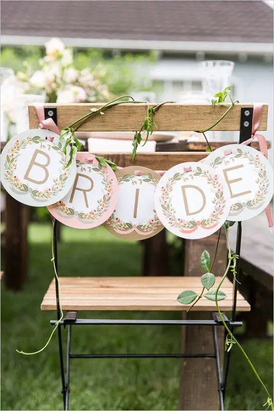 a letter banner with fresh greenery to decorate the bride's chair is a cute and easy to make idea
