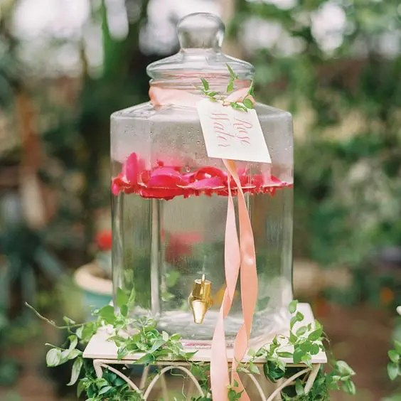 rose water in a large clear glass tank with ribbons, a tag and greenery is a great idea for a romantic garden shower