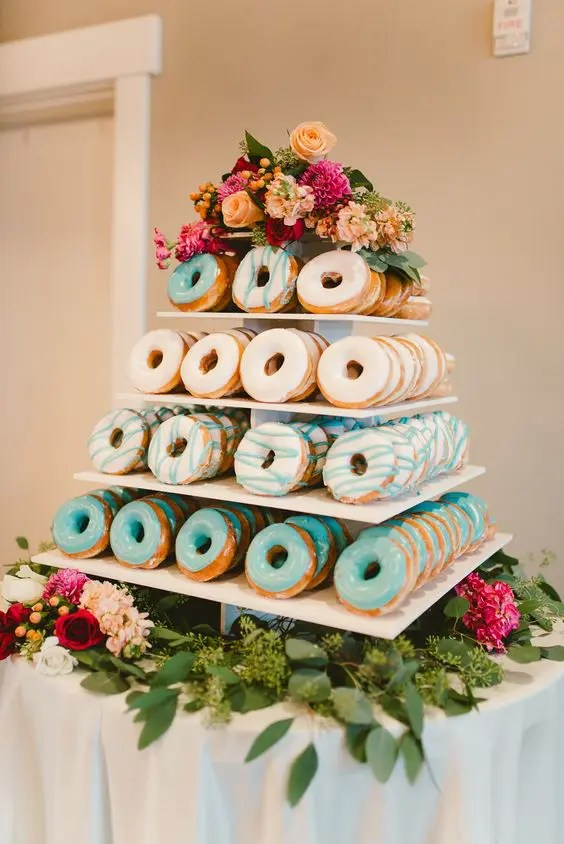 a glazed donut tower served on flowers and with flowers on top instead of a traditional wedding cake