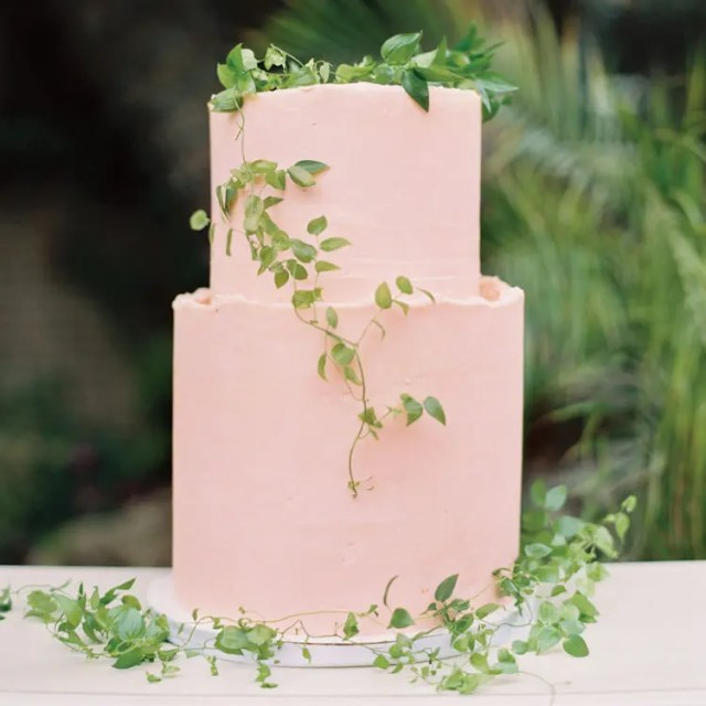 a light pink buttercream cake decorated with delicate greenery garlands on top and around is a cute idea for a dessert table
