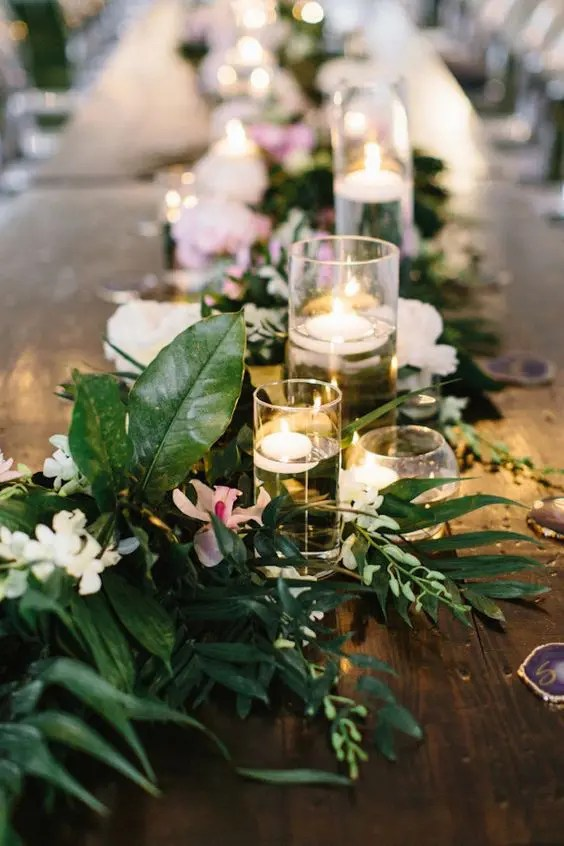 Picture Of a greenery tropical table runner with white and pink blooms plus floating candles in