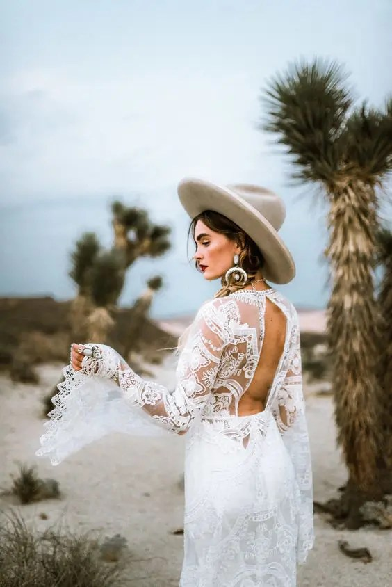 a boho coastal bride wearing a cutout back lace wedding dress and a neutral hat