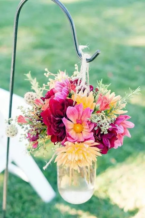 a bright floral arrangement in burgundy, pink and yellow wth herbs in a mason jar
