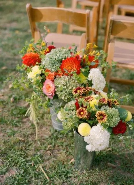 rustic floral arrangements in burgundy, red, yellow and white in buckets for a fall rustic wedding