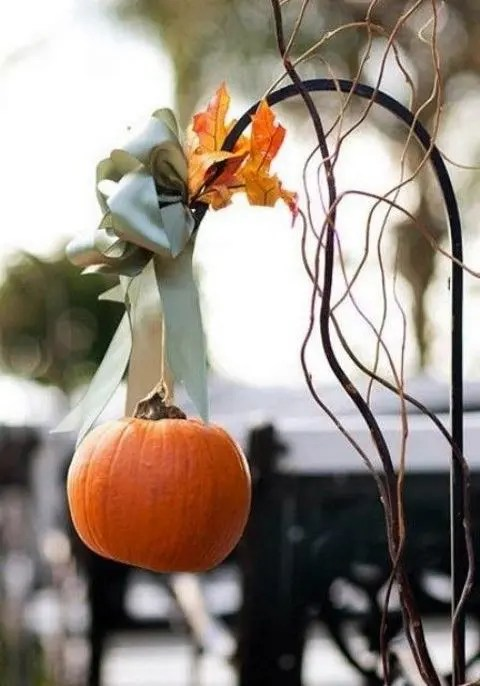 a cute little pumpkin with a green ribbon and leaves on a metal stand for a rustic feel