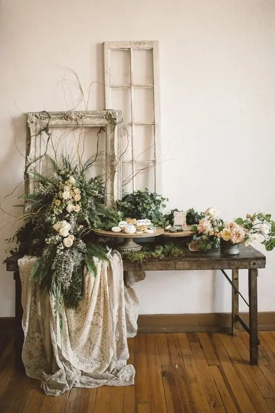 a rustic garden wedding dessert table with plenty of greenery and blooms and vintage frames plus lace