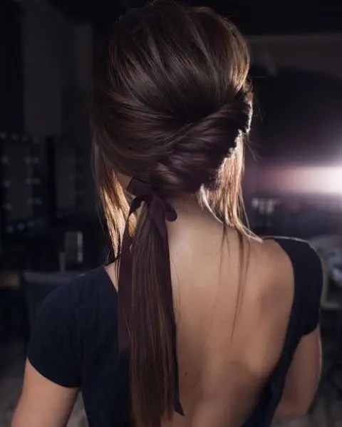 a low twisted ponytail with a bump, locks down and a ribbon is a chic modern option