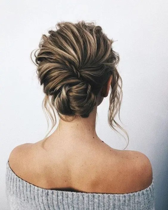 a chic textural messy low chignon with a twist and locks down looks elegant