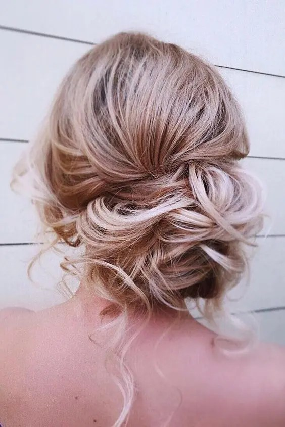 a messy curly low side bun with some curls down is a great idea for an effortlessly chic look