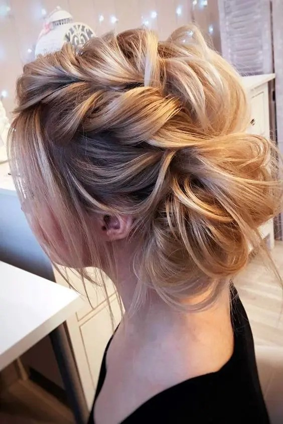 a voluminous messy braided updo with some locks down for a cute and glam look