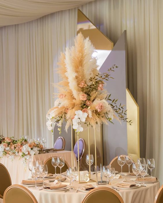 a creative wedding centerpiece of dusty pink roses, greenery and pampas grass on a tall gold stand