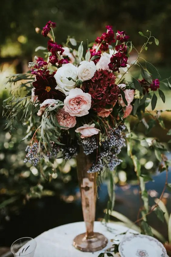 a lush floral centerpiece of burgundy, blush and white blooms, textural greenery in a gold vase
