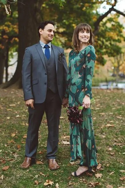 a dark green wedding dress with an emerald leaf print and long sleeves and dark green shoes for a fall look
