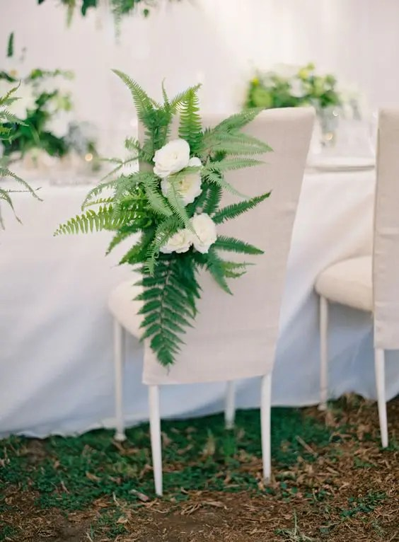a fabric covered chair decorated with ferns and white blooms is a creative idea