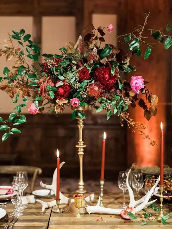 a luxurious wedding centerpiece of pink, red and burgundy blooms, greenery and dried leaves on a refined gold stand