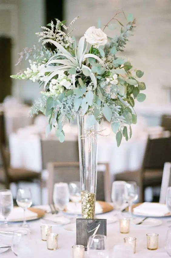 a modern tall centerpiece with a tall gold foil vase, eucalyptus, bluhs roses, herbs and air plants